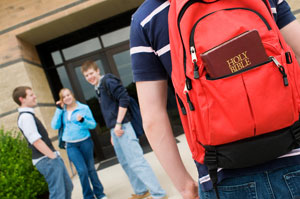 Child carrying bible to school in a backpack